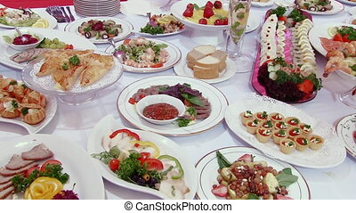Salads, meat, fish, fruit, strawberries on table.
