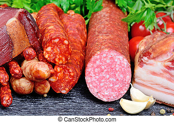 Salami, bacon and sausages with spices on table