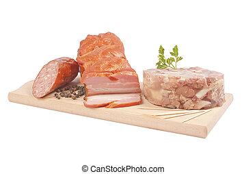 Salami, bacon, aspic on wooden board