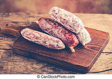 salami on rustic table - italian food concept
