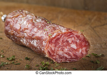 Salami on wooden cutting board with herbs