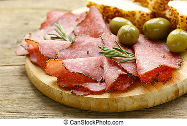 Salami pepperoni with aromatic pepper on a plate