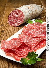 Salami sliced on wood background