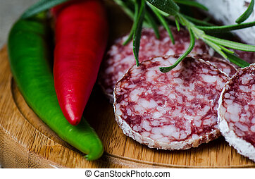 Salami with red and green pepper on wooden cutting board