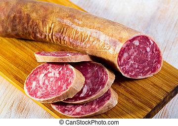 Salchichon spanish sausage slices on wooden desk