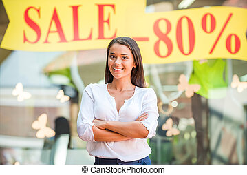 Sale! Beautiful young woman keeping arms crossed and smiling while standing against clothing store