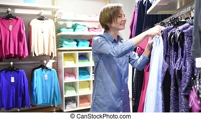 sale, clothes , shopping, people concept - happy young woman choosing between shirt and jacket at clothing store