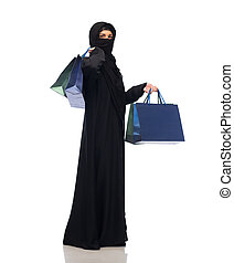 muslim woman in hijab with shopping bags - sale, consumerism...