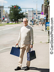 senior man with shopping bags walking in city