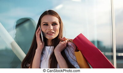 Sale, consumerism: Young woman with smartphones and shopping...