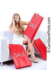 sale delight - Happy blonde woman enjoying her shopping with...
