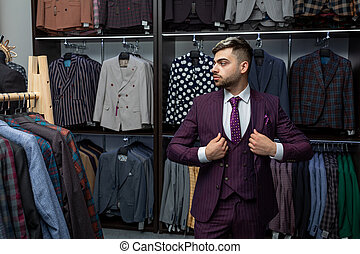sale, fashion, retail, business style and people concept - seriously hipster man with beard at clothing store. Advertising photo. Perfect to last detail. Model suit. Man in suit.
