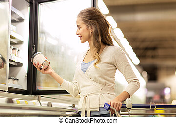 woman with ice cream at grocery store freezer
