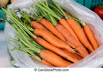 close up of carrot in plastic bag at street market - sale,...