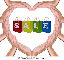 sale label on shopping  paper bag in hands heart