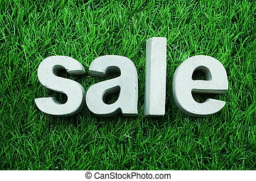 Sale made from concrete alphabet top view on green grass business concept