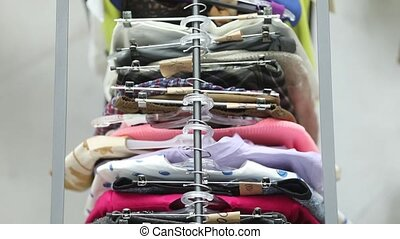 Sale of clothes on hangers among people from above - display...