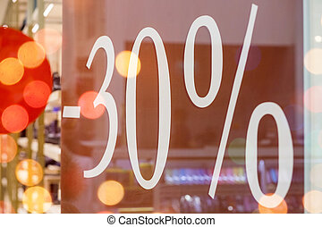 Sale. Shop window with 30 percent discount. Winter sale. Window shop with dressed mannequin, text Sale and 30 percent discount.Seasonal discounts in the store.New Year discounts.The final sale at a clothing boutique.