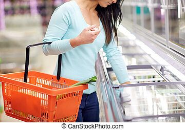 woman with food basket at grocery store freezer