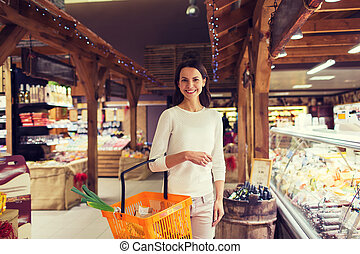 happy young woman with food basket in market