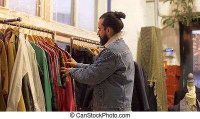 couple choosing clothes at vintage clothing store - sale,...