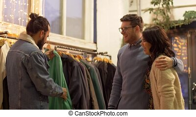 friends choosing clothes at vintage clothing store - sale,...