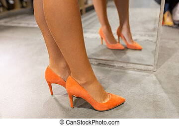 legs of woman in high-heeled shoes at store mirror