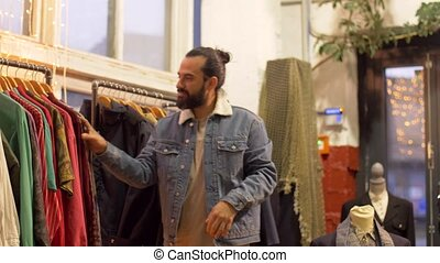 man choosing clothes at vintage clothing store - sale,...