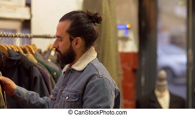 man choosing clothes at vintage clothing store