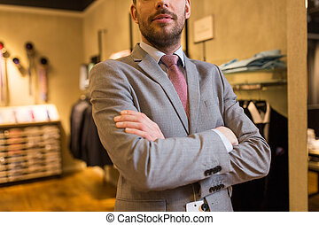 close up of man in suit and tie at clothing store