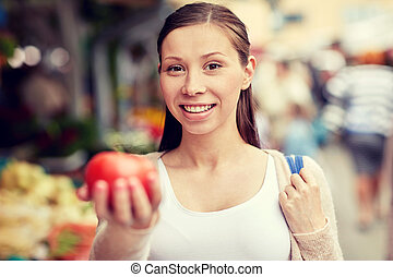 happy woman holding tomato at street market - sale,...