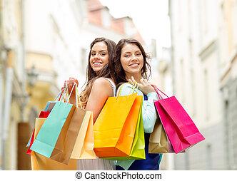beautiful women with shopping bags in the ctiy - sale, ...