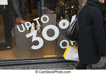sale sign and discount numbers on shop window of shoe store