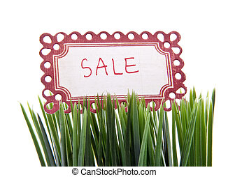 Sale Sign in Fresh Spring Grass Isolated on White with a Clipping Path.
