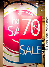 SALE Sign on the shop's window display. Boutique and Sale sign. Shop window display in the post about sales. announcement of a seventy-percentage discount on a glass show-window.