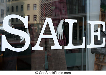sale text on shopping window - fashion store