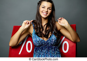 Sale time - Portrait of smiling brunette with sale paperbags...