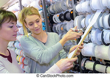 Sales assistant cutting length of ribbon for customer