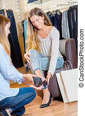 Sales assistant helping woman try a shoe
