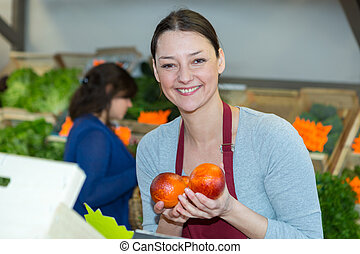 sales assistant holding blood oranges in a green grocers