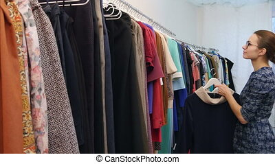 Sales assistant in clothing store fixing wardrobe