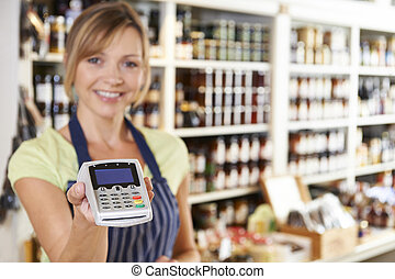Sales Assistant In Food Store Handing Credit Card Machine To...
