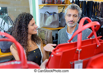 Sales assistant showing handbags to male customer