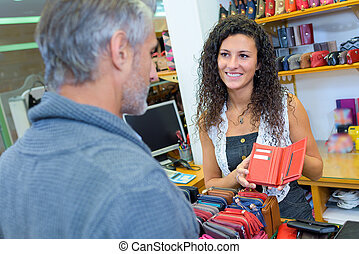 Sales assistant showing purse to customer