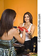 Sales clerk and customer. - African American women handing...