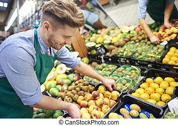 Sales clerk grabbing the box of fruits