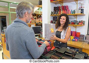 Sales clerk passing bag to male customer