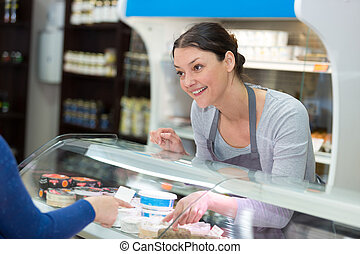 sales clerk serving at cheese counter