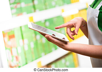 Sales clerk using tablet - Sales clerk wearing apron using a...