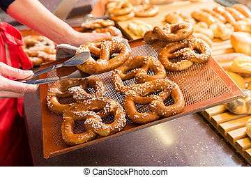 Sales lady in bakery shop selling pretzels and bread